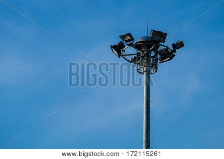 A part of top multi street light pole with blue sky background.