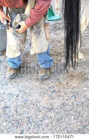 Male farrier working on a horseshoe inside a stable.