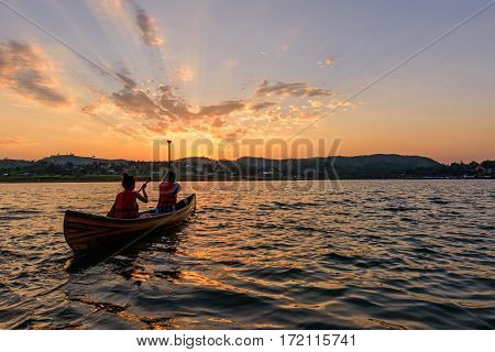 Unidentified traveler boating in the lake with sunlight