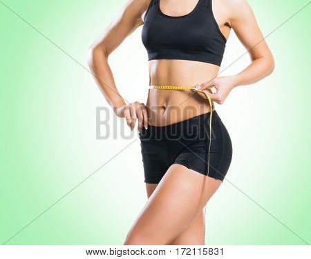 Fit, healthy and sporty woman in sportswear measuring her body over green background.