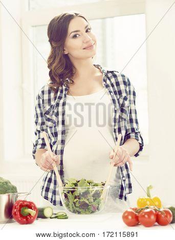 Beautiful pregnant woman preparing breakfast in kitchen. Motherhood, pregnancy, maternity concept.