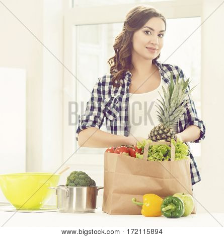 Beautiful pregnant woman with shopping bags in kitchen. Motherhood, pregnancy, maternity concept.