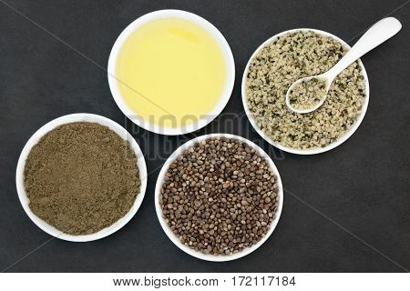 Hemp health food with oil, powder, dried and hulled seed in porcelain bowls with spoon on slate background.