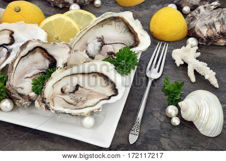 Oysters on ice with antique silver fork with lemon fruit, parsley herb, shells and pearls on a porcelain plate on marble.