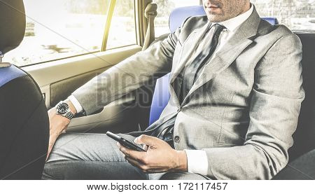 Young handsome businessman sitting in taxi cab while texting sms with smartphone - Business concept with modern man using smart phone - Soft vintage editing with artificial sunlight from window