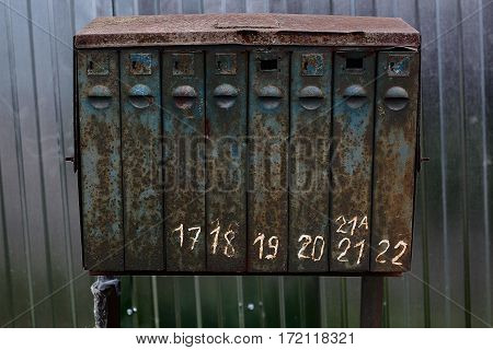 old rusty mailbox texture with numbers against the background of the fence in the countryside