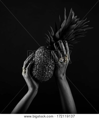 Dark-skinned Hand With Jewelry On A Black Background. Hands Holding A Pineapple.