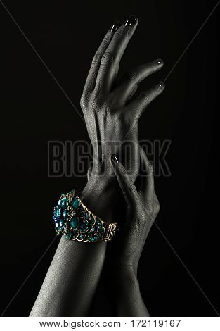 Dark-skinned Hand With A Gold Bracelet On A Black Background