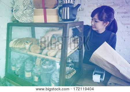 Young patisserie woman putting bread pastry on the shelf