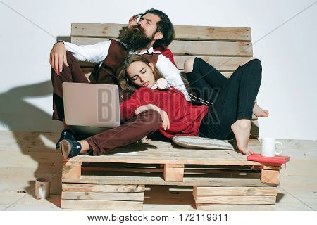 Young couple spend time together with laptop computer. Handsome man bearded hipster with beard sleeps near pretty girl or beautiful woman on wooden pallet sofa
