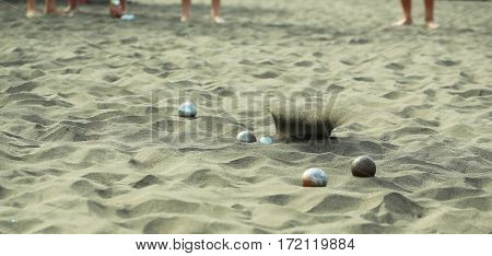 Bocce sport balls metal and plastic boules in natural sand on sandy beach outdoors on summer day on blurred grey textured background