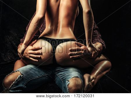 man holding hands on female sexy buttocks of young woman with slim body and legs with bare back in lingerie on dark background