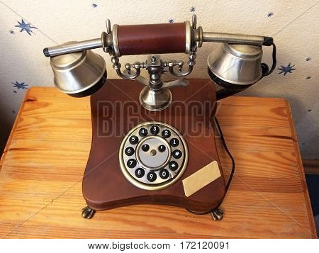 Rare vintage wired phone with round disc for dialing. Apparatus to transmit human speech at distance the telephone wire, made of wood and metal. Ancient technology - harbingers of modern development.