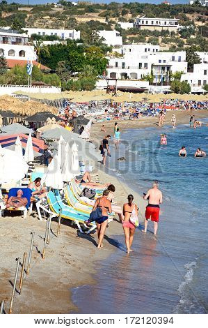 HERSONISSOS, CRETE - SEPTEMBER 17, 2016 - Tourists relaxing on the beach with views along the coastline Hersonissos Crete Greece Europe, September 17, 2016.