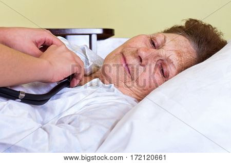 Picture of a bed ridden woman with her carer