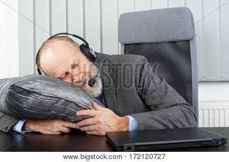 Picture of an overworked businessman sleeping at the office