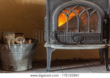 Winter at home. Fireplace with orange fire flame and firewood beside. Heating.