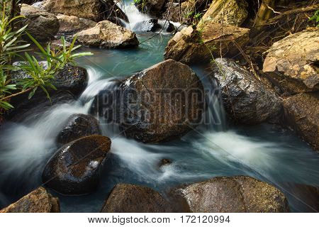 A landscape slow exposure river scene with large boulders and lush vegetation green in Vietnam.