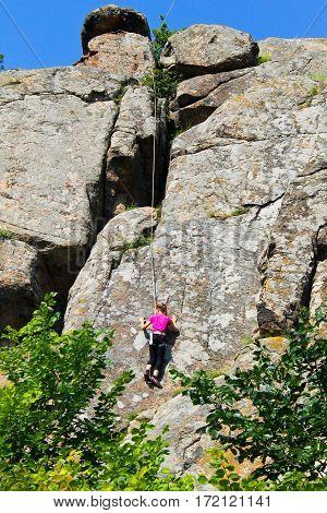 Girl rock climber climbs on a rock