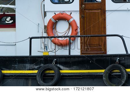 Side view of an old steel ship with lifebuoy in harbor.