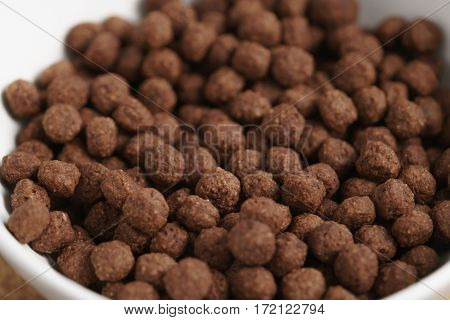 closeup of chocolate cereal balls in white bowl for breakfast on wooden table, shallow focus
