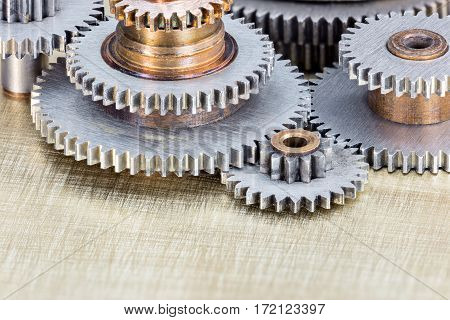 Various Cogwheels For Industrial Machines On Scratched Brass Background