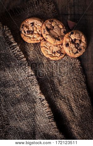 Chocolate cookies on dark napkin on wooden table. Chocolate chip cookies on brown coffee color cloth macro top view