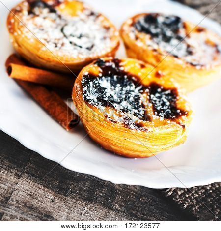 Egg tart - creamy sweet curstard on white plate on wooden table close up with copy space. Pasteis de Belem dessert