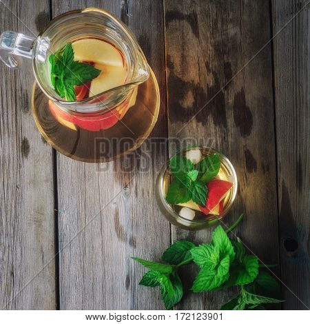 Tea with apples and mint in a jug and a glass