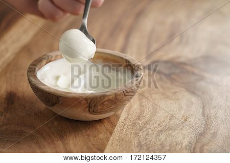eating with spoon homemade organic yogurt in wooden bowl on table, shallow focus