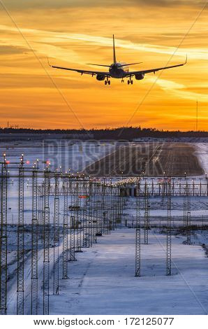 Commercial airliner landing to airport runway in sunset