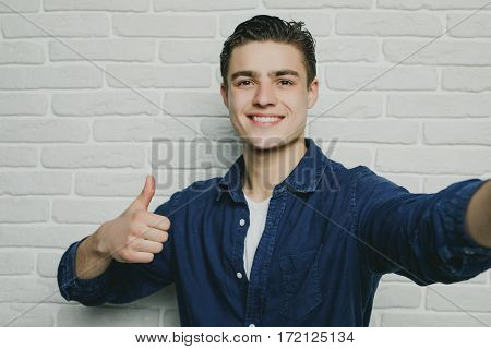Portrait of young goodlooking man against white brickwall.