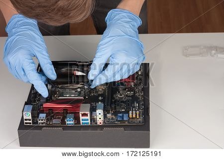 Young Man With Gloves Installing Part Of Cpu Cooler Fan.