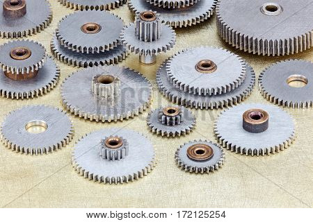Various Machinery Details, Gears And Cogwheels On Brass Background