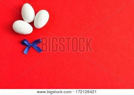 Three white easter eggs with a blue bow isolated on a red background