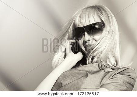 Young blond woman in sunglasses calling on mobile phone. Stylish fashion model outdoor