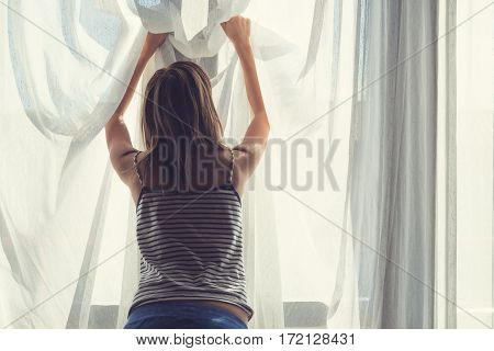 Silhouette of a Llonesome girl holding a curtain.