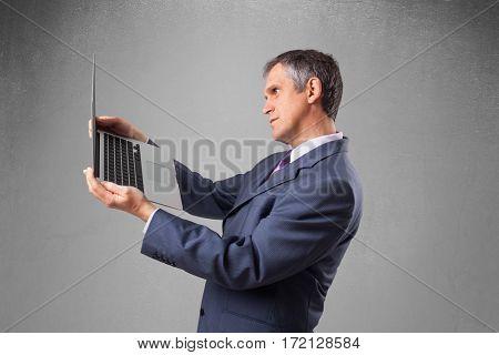 Handsome businessman in suit holding modern laptop