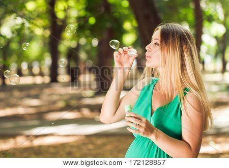 Happy Blond Pregnant Woman Blow Bubbles In Park