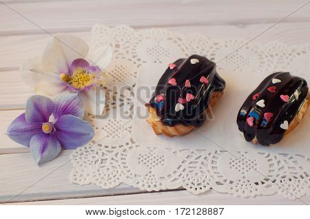 Chocolate eclair cakes with small white rose hearts above lay on serviette and white wooden table near two orchid flowers