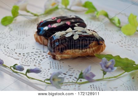 appetizing eclair cakes with dark chocolate cover and sprinkles lay on white lace serviette near fresh green flower stems