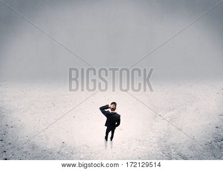 An adult elegant businessman standing in the middle of nowhere in empty grey concrete space background concept
