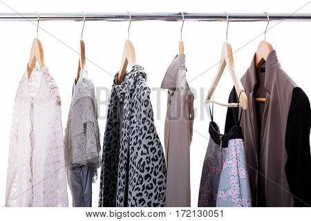 grey and beige womens clothes on wooden hangers on a rack on white background. closet business woman