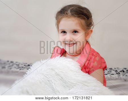 Portrait of funny little girl with his tongue hanging out. Baby smiling APE. White fluffy blanket. Pink dress
