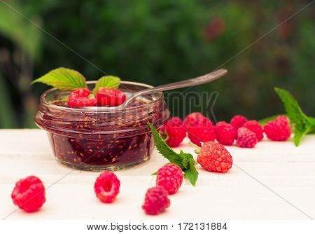raspberry jam in a jar and fresh berries on the wooden table