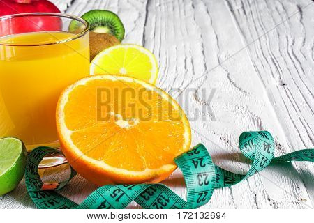 diet food with fresh fruits juice and centimeter on white background. weight loss and detox concept. close up
