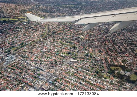 Sydney, Australia - Oct 29, 2016: Moments after plane takes off from runway. At Sydney Kingsford-Smith International Airport. Plane banks slightly to reveal surrounding suburbia.
