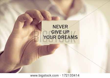 Businessman Holding Never Give Up Your Dreams Card