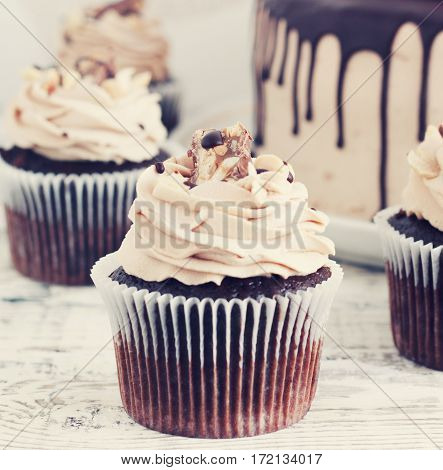 Chocolate cupcake with chocolate mousse cream icing on grunge white wooden background toning