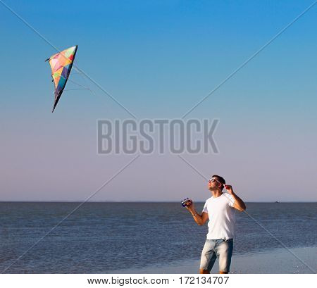 Happy young man with flying a kite on the beach. Summer time